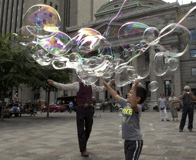 "Robert, who is known as ""The Bubble Wizard"", entertains kids with bubbles in Old Montreal, Friday, July 24, 2015, in Montreal. (Photo by Ryan Remiorz/The Canadian Press via AP Photo)"