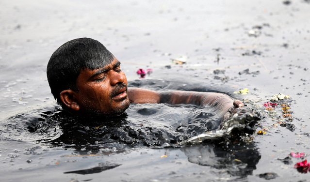 An Indian man looks for coins and other offerings, thrown by mainly Hindu devotees after their worship, in the polluted Yamuna River in New Delhi, India, 14 March 2018. On 14 March every year environmental activists globally hold the International Day of Action for Rivers with the aim of raising awareness around issues concerning the world's water ways. International Day of Action for Rivers was founded in 1997 in Curitiba, Brazil. (Photo by Rajat Gupta/EPA/EFE)