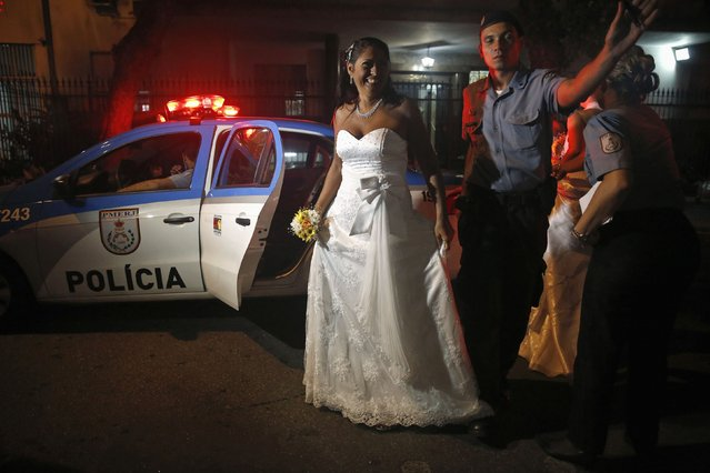 A bride from the Santa Marta slum is escorted by a police officer to her group wedding in Rio de Janeiro December 17, 2014. (Photo by Pilar Olivares/Reuters)