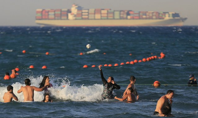 People play with a ball at the beach towards the end of summer vacation for schools, as a container ship crosses the Gulf of Suez towards the Red Sea before entering the Suez Canal, in El Ain El Sokhna, east of Cairo, Egypt, September 5, 2015. (Photo by Amr Abdallah Dalsh/Reuters)