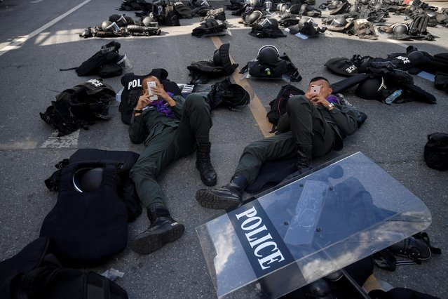 Police officers use their mobile phones near the Crown Property Bureau ahead of a pro-democracy rally demanding Thailand's King Maha Vajiralongkorn hands back royal assets to the people and reforms on the monarchy, in Bangkok, Thailand, November 25, 2020. (Photo by Chalinee Thirasupa/Reuters)