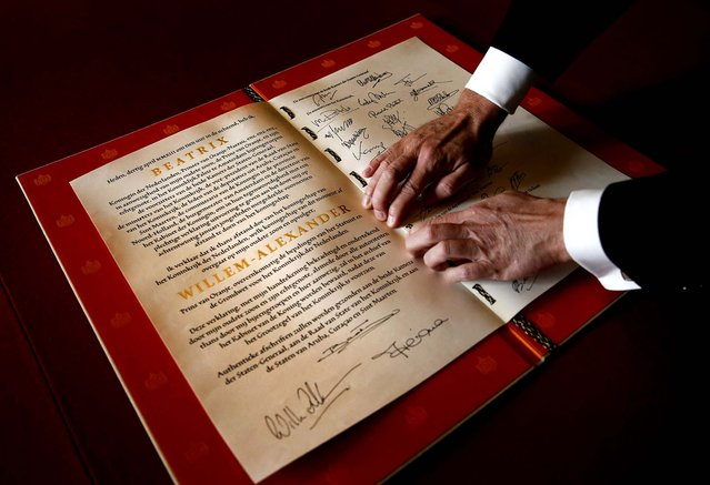 The Act of Abdication signed by Queen Beatrix, her son Prince Willem-Alexander and his wife Princess Maxima is displayed during the abdication ceremony in the Moseszaal at the Royal Palace in Amsterdam, on April 30, 2013. (Photo by Jerry Lampen/Getty Images)