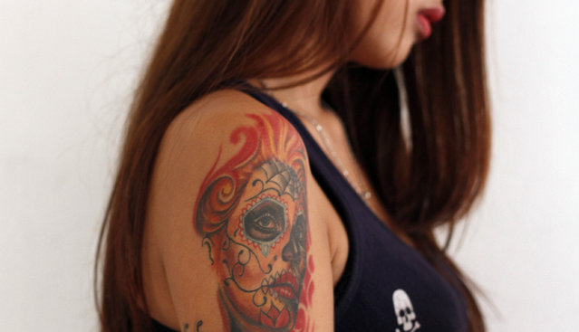 A tattoo is displayed on the arm of a girl during Bandung Body Art Festival at in Bandung, West Java, on December 7, 2014. Upon its establishment in 2010, founders of the Bandung Body Art Festival sought to celebrate an art form that was once taboo and associated with criminals. Tattoos are now an increasingly acceptable part of Indonesia's urban landscape, and the annual event this year continued its campaign with 45 tattoo artists offering their services for free at the Ganesha Cultural Center. (Photo by Rezza Estily/JG Photo)
