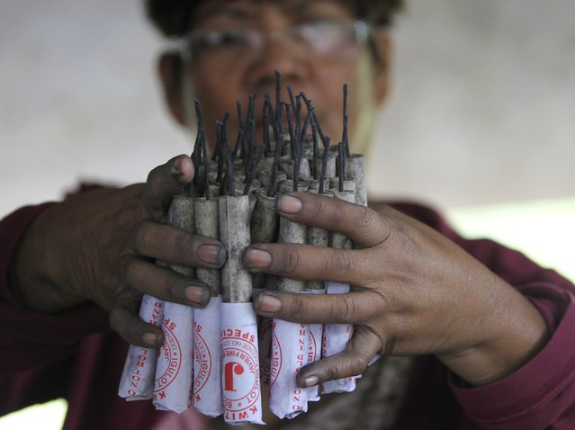 A worker inspects unfinished firecrackers as they make pyrotechnics at a makeshift factory in Bocaue town, Bulacan province, north of Manila December 27, 2014. Firecracker makers in Bulacan province, the pyrotechnic capital of the Philippines, are in haste to meet the demands for the coming New Year revelry. (Photo by Romeo Ranoco/Reuters)