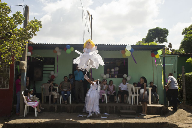 Guadalupe Bermudez tries to break a piñata, made in the likeness of an angel, during her first communion celebration in Managua, Nicaragua, Saturday, November 14, 2015. (Photo by Esteban Felix/AP Photo)