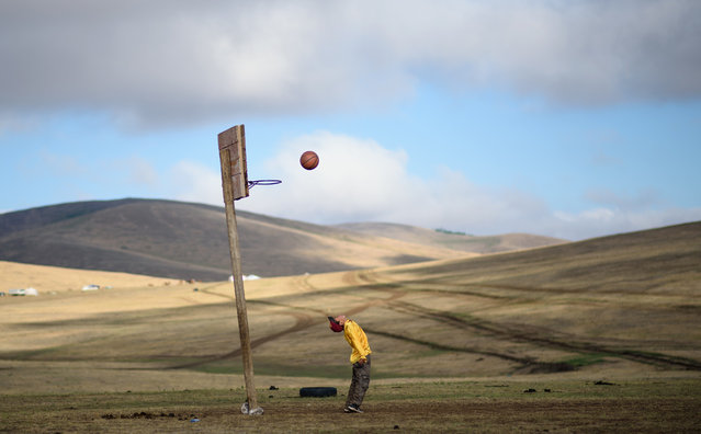 This picture taken on July 8, 2015 shows 13-year-old jockey Purevsurengiin Togtokhsuren playing basketball after taking care of the horses in Khui Doloon Khudag, some 50 kms west of Ulan Bator. (Photo by Johannes Eisele/AFP Photo)