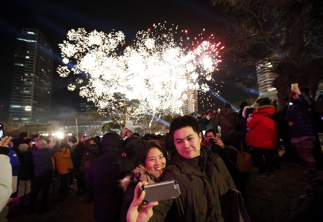"A couple takes a ""selfie"" as fireworks go off during a ceremony to celebrate the new year at Bongeun Buddhist temple in Seoul January 1, 2015. (Photo by Kim Hong-Ji/Reuters)"