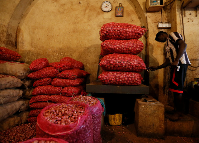 A man weighs sacks of red onions at a shop near a main market in Colombo , Sri Lanka September  30, 2016. (Photo by Dinuka Liyanawatte/Reuters)