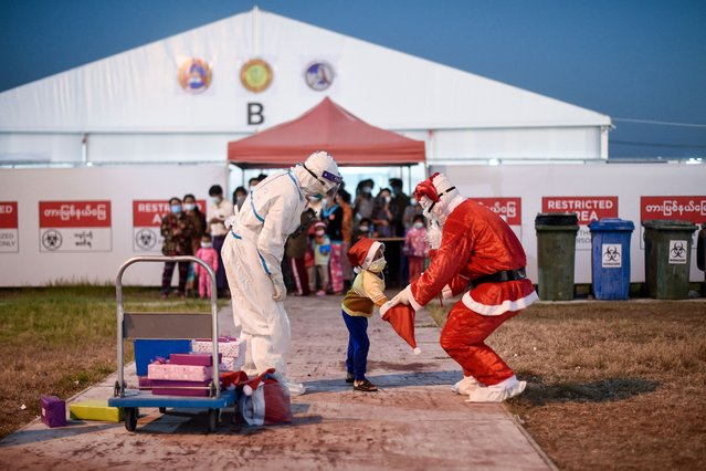 A healthcare worker dressed as Santa Claus distributes gifts to children at the Ayeyarwady Covid Centre in Mandalay, Myanmar, on December 25, 2020, Christmas Day, amid the Covid-19 pandemic, caused by the novel coronavirus. (Photo by Ye Aung Thu/AFP Photo)