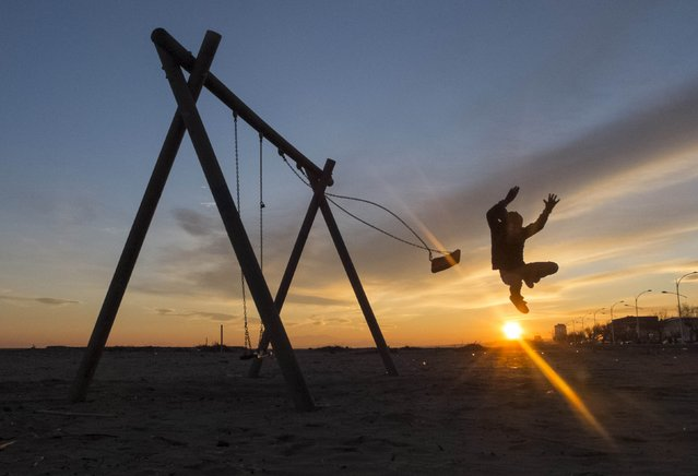 A boy jumps from a swing during sunset in Valras-Plage, southern France December 29, 2014. (Photo by Yves Herman/Reuters)