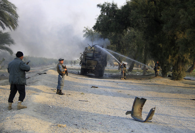 Afghan forces inspect the site of a roadside bomb explosion in Jalalabad, east of Kabul, Afghanistan, Monday, January 5, 2015. A roadside bomb hit a NATO convoy in eastern Nangahar province, damaging one vehicle but inflicting no casualties, spokesman Capt. Frank Hartnett said. (Photo by AP Photo)