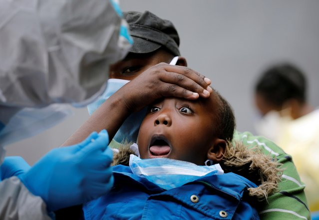 A young girl reacts as a Kenyan ministry of health medical worker takes a swab during mass tasting in an effort to fight against the spread of the coronavirus disease (COVID-19) in the Kawangware neighborhood of Nairobi, Kenya, May 2, 2020. (Photo by Baz Ratner/Reuters)
