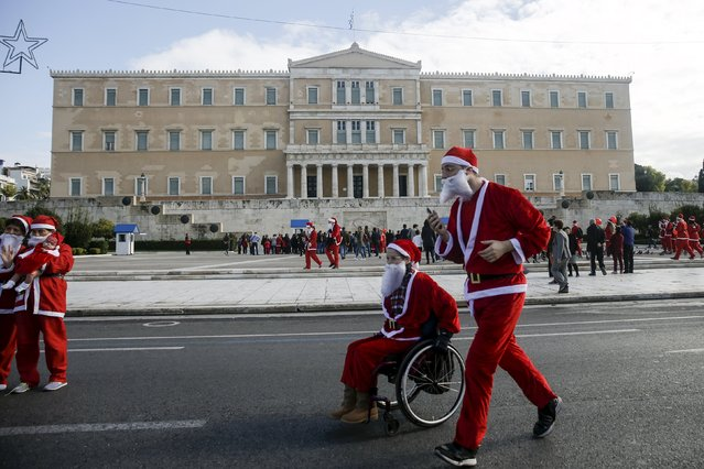 A person dressed in a Santa costume runs next to another in a wheelchair as they go past the parliament building during the Santa Claus Run in Athens, Greece, November 29, 2015. (Photo by Alkis Konstantinidis/Reuters)