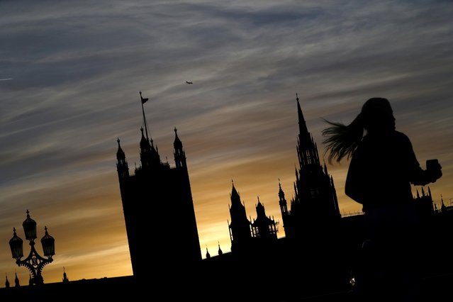 A person jogs as The Houses of Parliament is silhouetted at sunset in London, Britain, December 17, 2020. (Photo by Hannah McKay/Reuters)