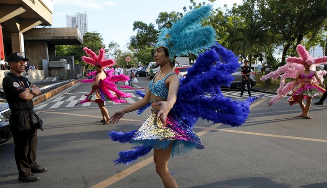 Traffic enforcers watch Filipino transgender women perform on a street during a World Aids Day celebration in Manila, Philippines, December 1, 2015. (Photo by Erik De Castro/Reuters)