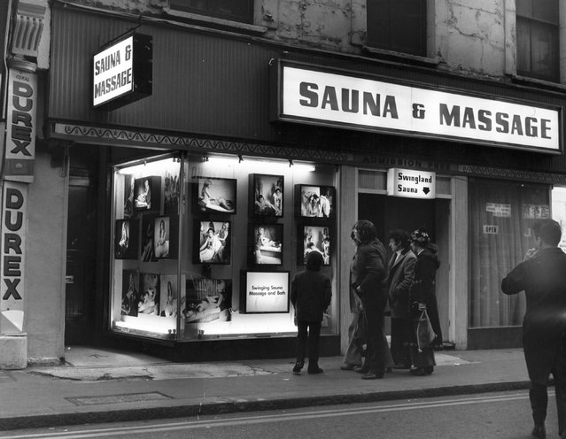 A group of men admire the photographs in the window of Swingland Sauna and Massage Parlour in Soho, London.   (Photo by Fox Photos/Getty Images)