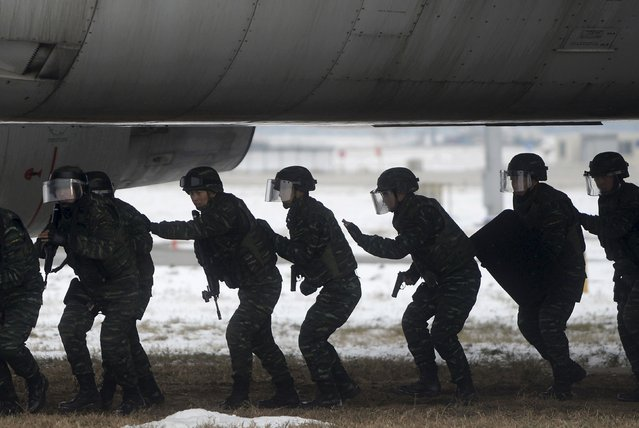 Armed paramilitary policemen walk underneath a passenger jet during an anti-terrorism drill on plane hijacking, at the Beijing Capital International Airport, in Beijing, China, December 3, 2015. (Photo by Reuters/Stringer)