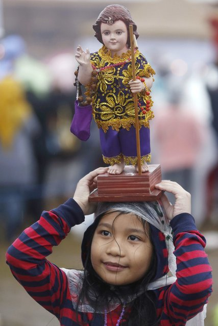 A Catholic faithful hold a religious statue during an open-air Mass led by Pope Francis at Rizal Park in Manila January 18, 2015. Pope Francis concluded his trip to Asia on Sunday with an open-air Mass for a rain-drenched crowd in Manila that the Vatican and the government said drew up to seven million people, the largest ever for a papal event. (Photo by Cheryl Ravelo/Reuters)