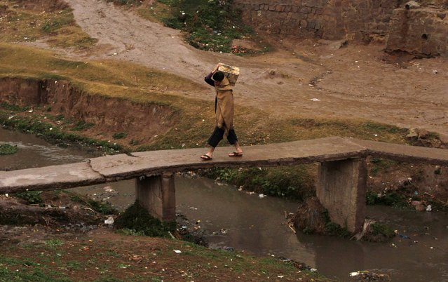 A man carries a fruit crate while crossing a bridge in a slum on the outskirts of Islamabad January 21, 2015. (Photo by Faisal Mahmood/Reuters)