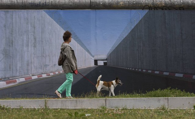 A woman walks past a picture showing a border fortification in the West Bank by German photographer Kai Wiedenhoefer at the former Berlin Wall in Berlin, July 11, 2013. Wiedenhoefer's Wall on Wall project consists of panoramic pictures of  eight border walls that separate people in different parts of the world. The pictures are currently displayed as 9x3 metre prints that Wiedenhoefer has pasted onto the longest remaining stretch of the former Berlin Wall border fortification. (Photo by Thomas Peter/Reuters)