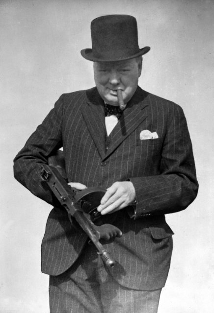This is a August 1, 1940 file photo provided by the British government, Britain's Prime Minister Winston Churchill tries a Tommy Gun during a visit to north-east England. Churchill Britain's famous World War II prime minister died fifty years ago on January 24 1965. The background behind Churchill has been blotted out by the censor. (Photo by AP Photo/British Official Photo)