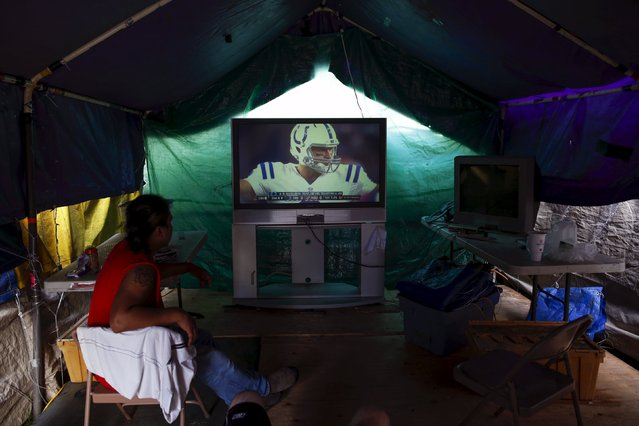 Tent city residents watch an NFL football game in their communal television area at SHARE/WHEEL Tent City 3 outside Seattle, Washington October 8, 2015. (Photo by Shannon Stapleton/Reuters)