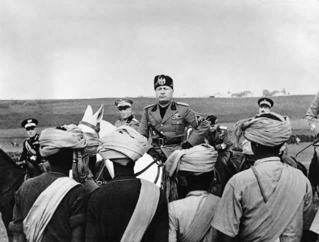 Italian Premier-dictator Benito Mussolini, center on horseback,addresses some of the troops from Italian Africa who are encamped on the outskirts of Rome, Italy, May 5, 1937. They are in Rome preparing for the celebration of the first anniversary of the Italian Empire, founded May 9, 1936. (Photo by AP Photo)