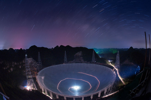 A vehicle leaves light trails in a long exposure photograph as it drives beneath the 500-metre Aperture Spherical Radio Telescope in Pingtang county, China. Construction on the device began in 2011 and is nearing completion. (Photo by Liu Xu/AP Photo)