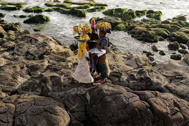 Girls stand on the rocks consulting a magazine as they carry their trays with fruits for sell, in Dakar, Senegal on February 28, 2021. (Photo by Zohra Bensemra/Reuters)