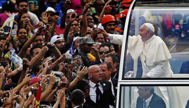 Pope Francis greets the crowd from his popemobile in downtown Rio de Janeiro. Pope Francis touched down in Rio de Janeiro on Monday, starting his first foreign trip as pontiff and a weeklong series of events expected to attract more than a million people to a gathering of young faithful in Brazil, home to the world's largest Roman Catholic population. (Photo by Ueslei Marcelino/Reuters)