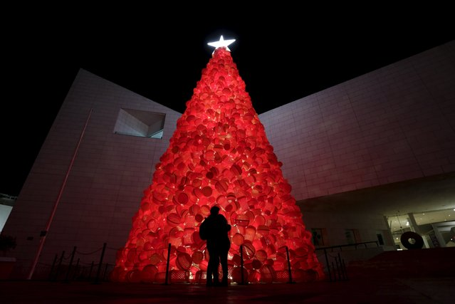 A couple hugs while standing near a Christmas tree made out of plastic bins and plastic hampers outside the Museum of History in Monterrey, Mexico, December 4, 2015. (Photo by Daniel Becerril/Reuters)