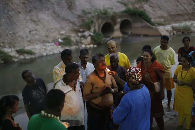 Hindu devotees say prayers before starting their pilgrimage to the Batu Caves temple during Thaipusam in Kuala Lumpur February 2, 2015. (Photo by Olivia Harris/Reuters)