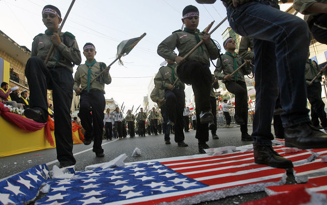 """Young boys of Hezbollah's al-Mehdi scouts stomp on a polystyrene sheet bearing the American flag, during a parade in the Lebanese southern suburb of Nabatiyeh, on August 1, 2013, to mark the """"Al-Quds (Jerusalem) International Day"""". An initiative started by Iranian revolutionary leader Ayatollah Ruhollah Khomeini, Quds Day is held annually on the last Friday of the Muslim fasting month of Ramadan and calls for Jerusalem to be returned to the Palestinians. (Photo by Mahmoud Zayyat/AFP Photo)"""