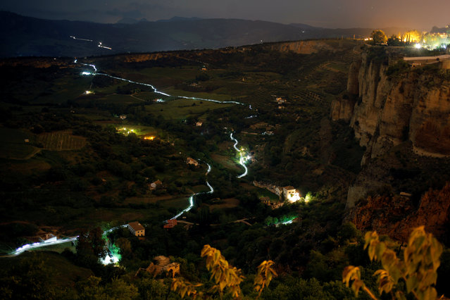 """Trails of headlamps are seen in the night as runners and mountain bikers make their way to the finish line (top R) as they participate in the XIX 101km international competition in Ronda, southern Spain, late May 14, 2016. About 8,000 participants, including runners and mountain bikers, ran a track of 101 km (63 miles) in less than 24 hours through the """"Serrania de Ronda"""" (Ronda Mountain Range) during the competition organised by the 4th Tercio (Regiment) """"Alejandro Farnesio"""" of the Spanish Legion. Picture taken May 14, 2016. (Photo by Jon Nazca/Reuters)"""
