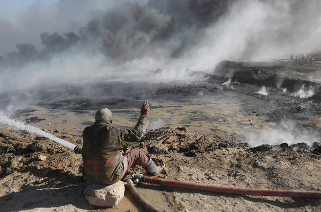 An oil worker gestures in front of oilfields burned by Islamic State fighters in Qayyara, south of Mosul, Iraq November 23, 2016. (Photo by Goran Tomasevic/Reuters)