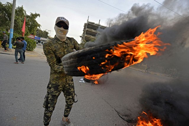 A masked demonstrator holds a flaming tire during clashes between anti-government protesters in Iraq's central holy shrine city of Najaf on March 15, 2021. (Photo by Ali Najafi/AFP Photo)