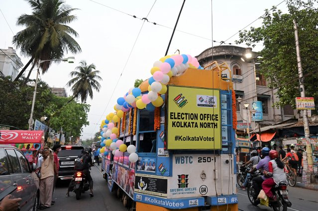 A tram decorated with posters of the ongoing state Legislative Assembly elections crosses a road in Kolkata on April 5, 2021. (Photo by Dibyangshu Sarkar/AFP Photo)