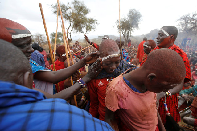 Maasai elders smear oil on children during an initiation into an age group ceremony near the town of Bisil, Kajiado county, Kenya on August 23, 2018. (Photo by Baz Ratner/Reuters)