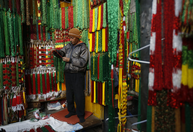 A vendor selling glass bead necklaces works at his stall along the streets of Kathmandu, Nepal January 5, 2016. (Photo by Navesh Chitrakar/Reuters)