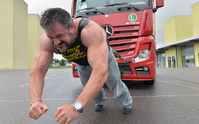 """Heinz Ollesch, for several times bearer of the title """"Strongest man of Germany"""", pulls a seven-tons truck on September 9, 2013 in Chemnitz, eastern Germany, to promote the German Truck Pulling Championships. The competition is scheduled to take place during the Commcar fair for commercial cars from October 12 to 13, 2013 in Chemnitz. (Photo by Hendrik Schmidt/AFP Photo/DPA)"""