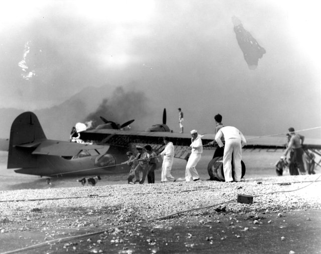 Sailors attempt to save a burning PBY amphibious aircraft at during the Japanese raid on Naval Air Station Kaneohe Bay,  Hawaii December 7, 1941. (Photo by Reuters/U.S. Naval History and Heritage Command)