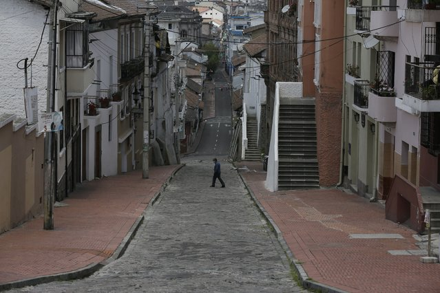 A downtown resident crosses a street free of pedestrians and traffic as a result of new lockdown restrictions due to the increase in COVID-19 infections, in Quito, Ecuador, Saturday, April 24, 2021. (Photo by Dolores Ochoa/AP Photo)