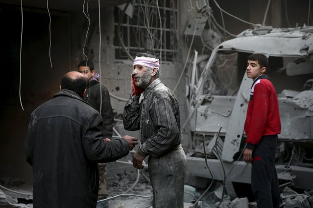 An injured man stands in a site hit by what activists said were airstrikes carried out by the Russian air force in the town of Douma, eastern Ghouta in Damascus, Syria January 10, 2016. (Photo by Bassam Khabieh/Reuters)