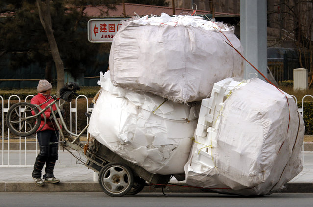 A recyclable materials collector stands in front of her overloaded tricycle on a main street in central Beijing March 12, 2010. (Photo by David Gray/Reuters)