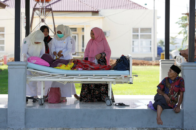A patient is treated in the outdoor walkway, for saftey reasons, at a hospital after a strong earthquake in Meureudu, Pidie Jaya, Aceh province, Indonesia December 8, 2016. (Photo by Darren Whiteside/Reuters)