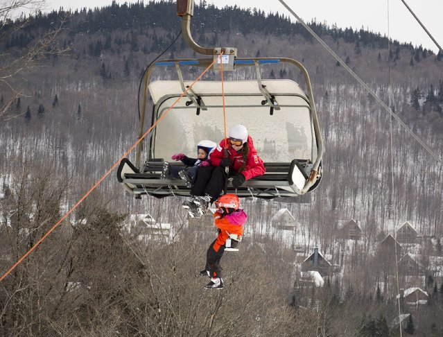 A child is taken down a chairlift in Stoneham, Canada, Saturday, February 21, 2015. The chair broke down and they had to evacuate the lift that was filled on a busy ski weekend. (Photo by Jacques Boissinot/AP Photo/The Canadian Press)