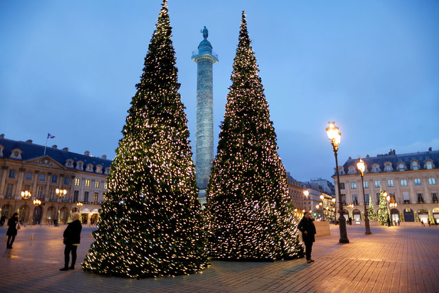 People stand near Christmas trees in front of the Vendome Column as part of Christmas holiday season illuminations at Place Vendome in Paris, France, December 11, 2016. (Photo by Charles Platiau/Reuters)