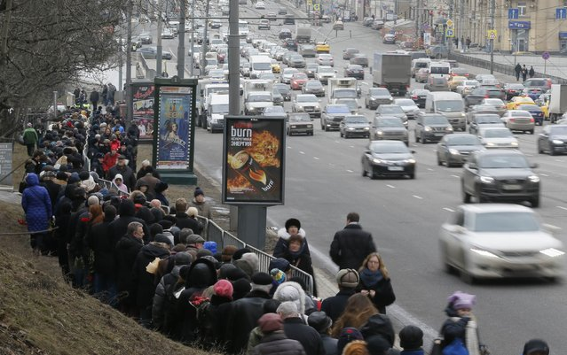 People stand in line to attend a memorial service before the funeral of Russian leading opposition figure Boris Nemtsov, with vehicles driving nearby, in Moscow, March 3, 2015. Several hundred Russians, many carrying red carnations, queued on Tuesday to pay their respects to Boris Nemtsov, the Kremlin critic whose murder last week showed the hazards of speaking out against Russian President Vladimir Putin. REUTERS/Maxim Shemetov
