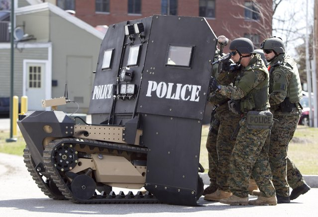 A SWAT robot, a remote-controlled small tank-like vehicle with a shield for officers, is demonstrated for the media in Sanford, Maine, on, April 18, 2013. Howe & Howe Technologies, a Waterboro, Maine company, says their device keeps SWAT teams and other first responders safe in standoffs and while confronting armed suspects. (Photo by Robert F. Bukaty/AP Photo)