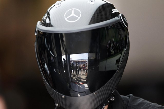 The pit lane is reflected in the visor of a Mercedes Formula One pit crew member during the second practice session of the Australian F1 Grand Prix at the Albert Park circuit in Melbourne March 13, 2015. REUTERS/Brandon Malone